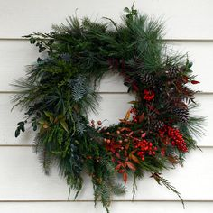 asymmetrical wreath with evergreen tree boughs and a shot of red berries
