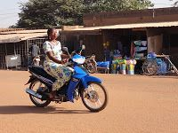 Throughout Ouagadougou, the capital city of Burkina Faso, women in beautiful dresses and shiny high heeled shoes ride motorcycles for transportation. Many times they ride double with a friend or family member and additional cargo or children.