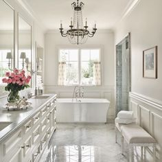The use of wainscoting in the master bathroom softens the Carrara marble floors and counter by Goodall Custom Cabinetry & Millwork. The Eloquence reproduction bench and Visual Comfort & Co. chandelier create a French feel. The luxurious soaking tub is by Kohler.
