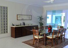 Na sala de jantar, a mesa com tampo de vidro reúne até oito pessoas para as refeições indoor. Um buffet em madeira e mármore completa o ambiente.