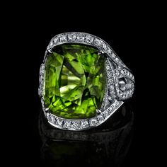 An 18ct green peridot gem is set in expert hand crafted 18K white gold and framed by 2.25cts tw of intricate white diamond pave.