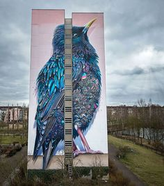 Earlier this year, Netherlands-based artists Super A and Collin van der Sluijs teamed up to create a stunning 137-foot tall mural on the side of a building in Berlin. Titled 'Starling', the mural shows a massive blue and purple bird covered in feathers. But when you take a closer look, you'll see it's covered in not only feathers but all sorts of different jewels and gems.