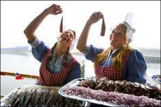 Twee haring dames testen de Hollandse Nieuwe. Foto: Robin Utrecht/ANP