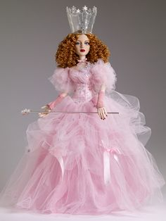 "Glinda the Good Witch - 75th Anniversary Collection! Featuring the glorious 19"" Evangeline Ghastly body from Wilde Imagination, this Glinda is all glam! Including graceful hand-painted features, silky cameo skin tone, a mane of rooted strawberry tresses, and blue painted eyes behind thick lashes, Glinda is a remarkable beauty worthy of munchkin love. Wearing a frothy pink gown with bow, star and butterfly detail, pink and silver gauntlets, ribbon choker and glittery crown of rhinestones...."