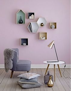 Pastels colors are used.Focus goes on the wall which has different geometric shelves. The golden lamp and vase are going with the squared shelves.Its a well balanced frame.