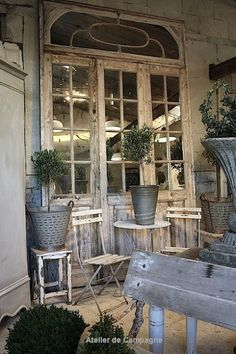 weathered doors and furniture.  topiaries in galvanized pots