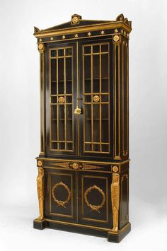 English Regency Style Black Lacquered And Gilt Trimmed Bookcase Cabinets With 2 Upper Glass Doors And 2 Lower Doors With Gilt Applied Wreaths  c. 19th Century