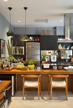 cuisine bois clair, murs en bleu pastel, meubles en noir, luminaires suspendus en gris métallique, sol en beige, deux chaises aux dossiers bas, avec des coussins blancs