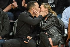 John Legend and Chrissy Teigen share a courtside kiss on Thursday in Los Angeles.