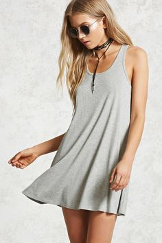 A ribbed knit dress featuring a scoop neck, racerback, and a swing silhouette.