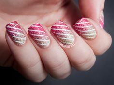 Gold, red, and pink striped, glittery manicure