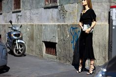 Russian blogger Maria Kolosova wearing black midi dress and lace-up heels after a fashion show in Milan