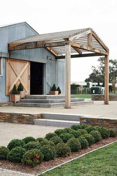A convertedbarn with attached pergola and manicured boxwoods along the pathway.