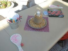 Guest tables for a western BBQ party - covered in craft paper, bucket of markers to write on the table, decks of cards, checkers, paddle ball, & paper games like tic-tac-toe & hangman. Centerpiece = mason jar filled with popcorn - jar wrapped with burlap  tied with twine, set in a pie tin of raw popcorn.