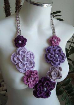 Um lindo colar em crochê com flores em vários tons de lilás, roxo e uva. Uma corrente dá um charme especial à peça. Pode ser feito em outras cores: Consulte * COMPRE COM DEPOSITO EM CONTA E GANHE 7% DE DESCONTO: Consulte R$ 85,00