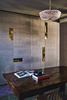 Derrière la table de la salle à manger, chinée, une chaise vintage d'Harry Bertoia (Knoll). Sur les portes des placards, recouvertes du papier peint Babinda (Fromental), les poignées surdimensionnées en laiton sont des éléments décisifs de la décoration de la pièce. Suspension en verre de Murano années 1940 de Barovier & Toso.
