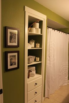 Behr grape leaves green and white bathroom. White shower curtain from target. bathroom built in shelves and decorations. framed baby pictures in the bathroom.