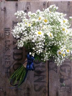 bridesmaids hand tied bouquet of delicate gypsophila and  tanacetum daisy's finished with a band of hessian and navy blue ribbon trails.