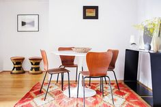 This apartment enlists pattern in a subtle way. Though the orange-red rug is bright, it matches the chairs, works with the floor, and makes the white walls feel open and airy.Designer: Matt Merrell. #refinery29 http://www.refinery29.com/homepolish/71#slide-1