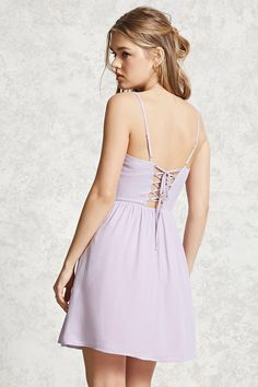 A woven fit and flare dress featuring a lace-up back, a square neckline, adjustable cami straps, an elasticized back waist, and a hidden side zipper.