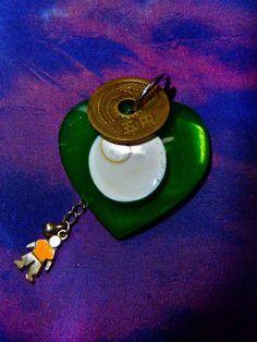 Cœur en plexi vert avec inclusion d'une spirale de nacre et pièce japonaise. 35 €
