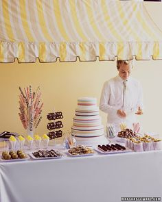 "The fanciful quality of this buffet will instill childlike anticipation in every guest. Treats are playfully displayed on stands and sticks and in cups and bags, as they would be at an old-time carnival. The striped awning, in muted candy colors, echoes the swirled lollipops, rock candy, taffy, and fondant ""ribbons"" on the cake."
