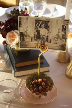 DIY Wedding Decor by FrugElegance~ Bride & Groom printed photos of places they had travelled for table assignment names placed in vintage tea cup we shopped for #DIY wedding #wedding decor #wedding table numbers