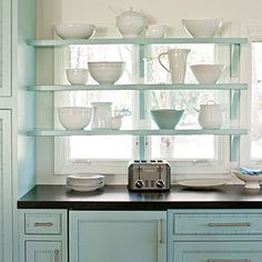 Open shelving hanging in front of these kitchen windows provides added storage space while still allowing light to pass through. | As seen in southernliving.com | thisoldhouse.com
