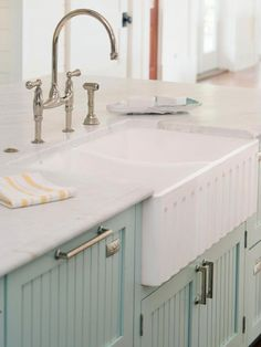 Beautiful seafoam green cabinetry housing a country style apron sink... Traditional Coastal Style Kitchen Design Inspiration   DigsDigs