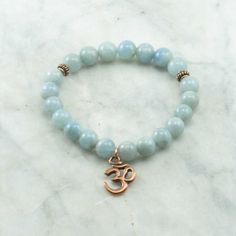 The Sea Mala Bracelet is made from 21 aquamarine mala beads. Copper beads are added for color. It is completed with a copper OM charm. This Buddhist Bracelet is best for: Soothing, calming, cooling, a