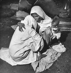 Margaret Bourke-White: INDIA, 1947 -- A grieving Moslem mother holds her child while hugging a family member at the gravesite of her 4-year-old child who died of starvation when their Pakistan special train was stopped for four days by Sikh attacks during their migration from India to Pakistan.