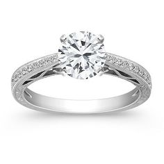 Twenty round pavé-set diamonds, at approximately .09 carat total weight, serve as accents to the center diamond of your choice in this elegant vintage-inspired engagement ring which is part of our Annata collection.  Each stone has been hand-selected for fire and sparkle, and is set in superior quality 14 karat white gold with engraved detailing. Shown with a center stone Brilliant Round Diamond.