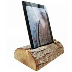 Natural Wood Tablet & iPad Nightstand Holder with bark or barkless options available. We also have a beautiful flat bottom option available with this product. Our wood tablet stand includes a plug hole for charging in the middle and routed on the bottom - no plug included, pull the plug through to plug into the tablet, then set it onto the stand. The plug hole is about 1/2 wide and fits usb sized cables. Have a custom plug? Let us know and we will drill a custom size for you.
