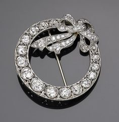 An Edwardian diamond circle and bow brooch  set throughout with European-cut diamonds; estimated total diamond weight: 3.50 carats; mounted in platinum; length: 1 1/2in.