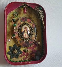 Beautiful Madonnas shrine - the earth is my mother I make these shrines out of old tin cans, I think that thats great as a framework. They are ground off of me and painted in many thin layers. This shrine is dark in various layers of paint to a shabby. Magenta painted and lined with a vintage fabric in yellow, a dark gold trim and a green cord. The picture of the Madonna under a glass cabochon (25 x 18) resting on a self designed large oval medallion. There are many fine decorations…