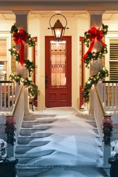 Gorgeous front porch decorated for Christmas, check out he colums, wrapped wwith greenery and lights