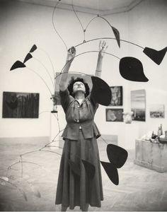 Peggy Guggenheim adjusting a Calder mobile.