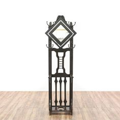 This hall tree is featured in a solid wood with a dark espresso finish. This bohemian style coat rack has carved splats, diamond-shaped mirror, and 4 hooks. Perfect for hanging hats, umbrellas, and more! #bohemian #storage #halltree #sandiegovintage #vintagefurniture