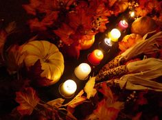 Candles glow through dried corn, Autumn leaves and pumpkins