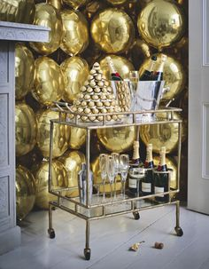 Grid a wall with gold balloons to make a striking festive backdrop. A drinks trolley is the ultimate New Year's Eve party centrepiece. Image: Livingetc