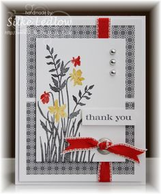 Love how the red ribbon pops through the silver eyelet to create a knotted bow on the card front. Small pops of red on some of the flowers tie it all together. Handmade thank you card