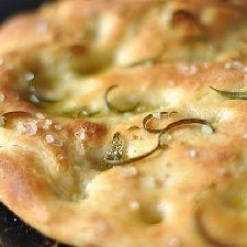 Ricetta Focaccia al rosmarino, una delle focacce morbide più amate, insaporita con il rosmarino e il sale grosso. Ricetta e consigli impasto e cottura.