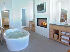 I'm not usually one for a TV in the bathroom, nor a fireplace, but THIS looks pretty inviting!