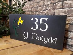 Our beautiful Welsh slate house signs are handcrafted in our Crynant workshop and only take up to two weeks to make. We have a range of styles, fonts & colours for you to choose from as well as our motifs, like the daffodil on this sign.