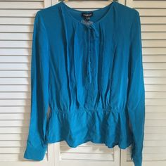 BEBE Silk Blouse BEBE blue silk button down blouse with cinched waist. Long sleeves have option to be rolled up & buttoned into 3/4 sleeves. Has original extra button. NEW WITHOUT TAGS ~ NEVER WORN!!! bebe Tops Button Down Shirts