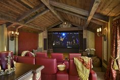 Stunning rustic home theater by Locati Architects with red theater chairs and exposed wood cathedral ceiling.
