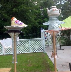 Multi-colored bird perched on a saucer and little teapot whimsies