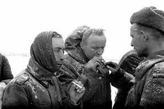 A Soviet soldier gives cigarettes to German POWs captured during the Battle of Stalingrad. Stalingrad (now Volgograd), Volgograd Oblast, Russia, Soviet Union. January 1943.