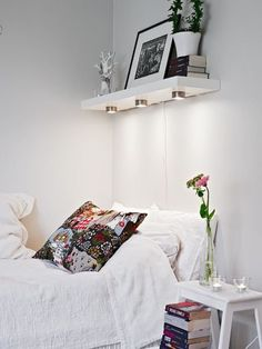 Floating shelf above bed for storage with lights mounted underneath for reading