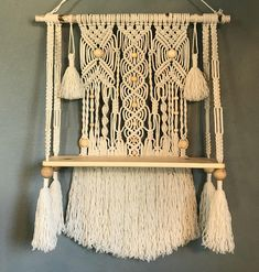 This is a macrame wall hanging with a natural wood shelf attached. The shelf measures x x The macrame is attached to a birch branch measuring wide. The macrame design measures x and is made with cotton rope in a lamb's wool color. Macrame Design, Macrame Art, Macrame Projects, Macrame Knots, Bohemian Wall Art, Bohemian Decor, Wall Hanging Shelves, Macrame Curtain, Macrame Tutorial